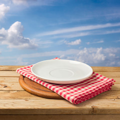 Plate and tablecloth on wooden table over blue sky