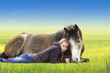 Girl and horse lying and sleep on sunny summer field