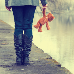 lonely girl with teddy bear near river