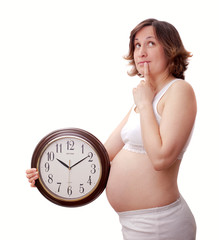 Young toughtfull pregnant woman with clock