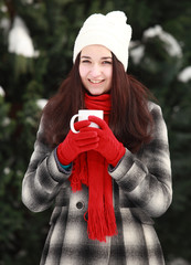 Woman holding hot coffee or tea outdoors in winter