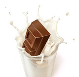 Chocolate block falling into a glass mug full of fresh milk