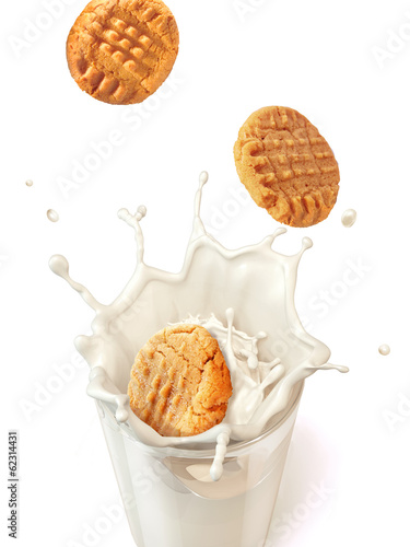 Three cookies biscuits falling into a glass mug full of fresh mi