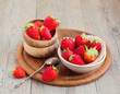 Strawberries in plates on wooden table