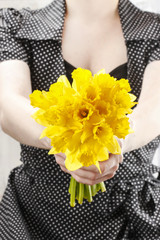 Woman holding bouquet of fresh daffodils