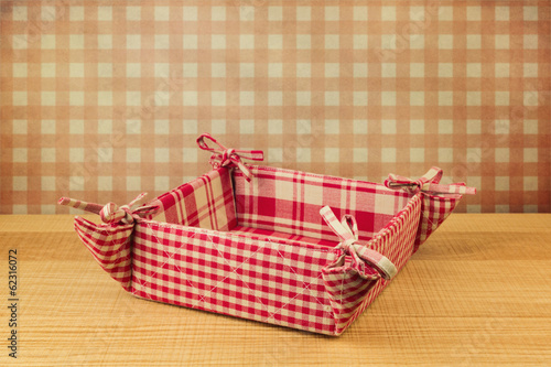 Basket on wooden table over retro wallpaper