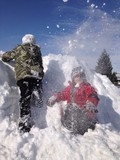 snowball fight while two boys climb snow pile