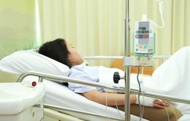 Patient in hospital bed with medical infusion drip tool