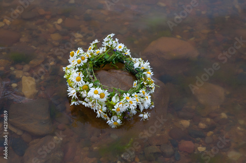 Beautiful wreath with summer flowers in the water.