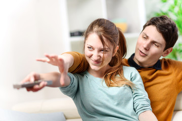 beautiful couple bickering to change tv channel on remote contro