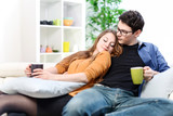 Cheerful couple relaxing together on sofa in living room