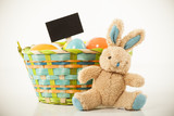 Easter Bunny sitting beside a basket full of eggs that has a sig