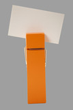 orange clothes pin holding a note with gray background