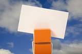 orange clothes pin holding a note with cloudy sky background