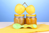 Jars of baby puree with spoon on napkin on blue background