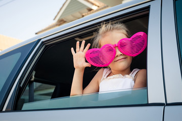 girl with big glasses sitting in the car