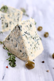 Tasty blue cheese with thyme and olives on wooden table