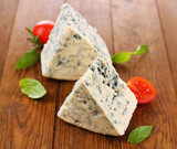 Tasty blue cheese with basil and tomato, on wooden table