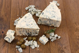 Tasty blue cheese with olives, on wooden table