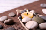 Composition with spa stones, candles on bamboo mat background