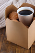 Hot coffee and cookies in box on wooden table close-up