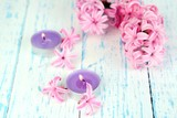Pink hyacinth with candles on wooden background