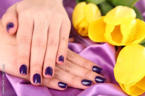 Beautiful woman hands with flowers on fabric background