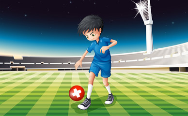 A male soccer player kicking the ball with the flag of Switzerla