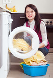 Brunette woman loading clothes into the washing machine