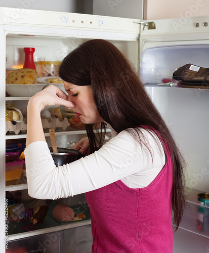 woman holding  nose because of bad smell from food