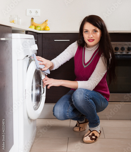 brunette woman cleaning washing machine
