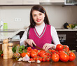 Happy woman cutting  tomatoes