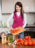 woman cooking with tomatoes in home