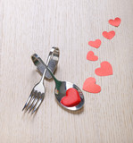 Red heart with fork and scoop on wooden background