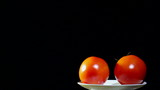 Two tomatoes  turns on  white plate, black background
