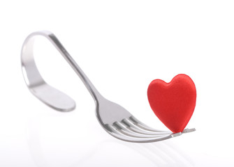 Red heart with fork on white background