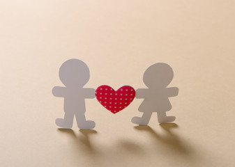 Silhouettes of men, women and heart cut out of paper on a wooden