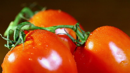 three tomatoes  with water drops in rotation. Close up