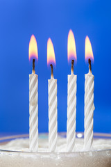 Burning white candles over blue background