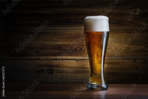 Fotobehang Bier beer glass on a wooden background