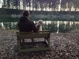 Mann mit Hund auf Bank