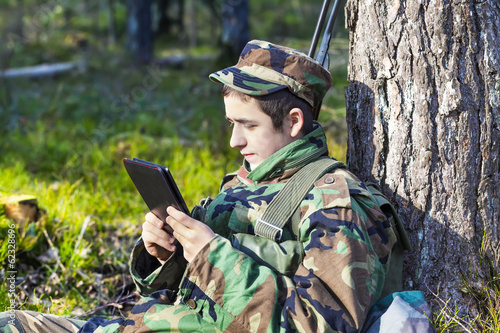 Recruit with tablet pc in forest near tree