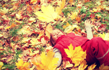 child lies in autumn leaves