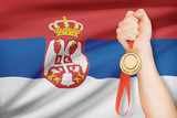 Medal in hand with flag on background - Republic of Serbia