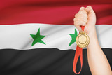 Medal in hand with flag on background - Syrian Arab Republic