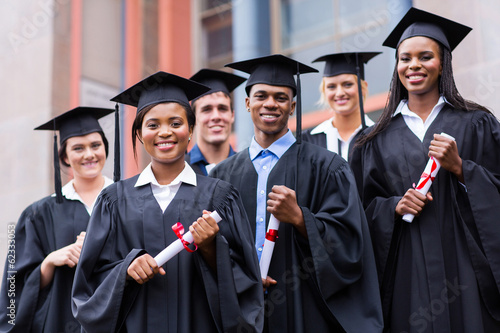 young graduates standing in front of university building