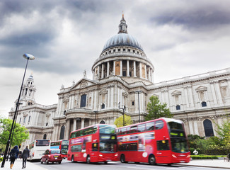 St Paul's Cathedral in London, the UK. Red buses, cloudy sky
