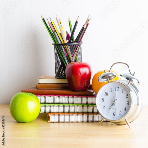 Back to school , note book , clock , pencil , apple on wood tabl