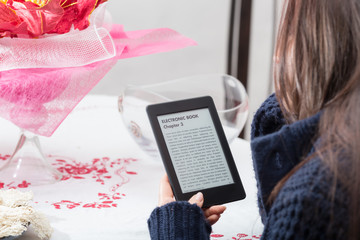 Girl is reading a book with an e-book reader