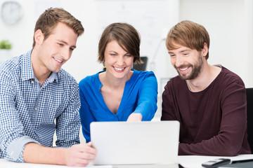 drei kollegen schauen auf laptop